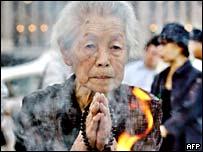 An elderly woman prays in Hiroshima Peace Park