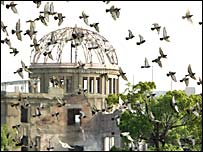 Doves fly above the Atomic Dome in Hiroshima Peace Park