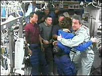 Discovery Commander Eileen Collins hugs ISS astronaut John Phillip