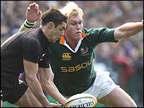 South Africa flanker Schalk Burger (right) pressurises All Blacks fly-half Dan Carter