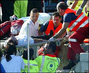 Rescuers carry an injured victim of the plane