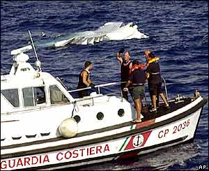 The wreckage of the plane is seen as an Italian Carabinieri boat navigates past it