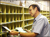 Post Office worker sorting mail