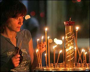 Una mujer prende velas en una iglesia de San Petersburgo para pedir por la vida de los marinos.