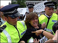 A protester is taken away by police