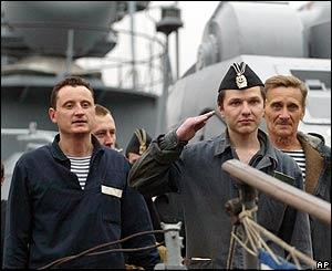 El comandante del mini submarino AS 28 saluda al frente de sus hombres.