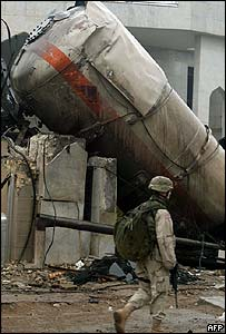 A US soldier walks past the tanker wreckage