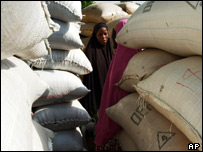 Two girl talk near piles of bags of groundnuts in Maradi, Niger