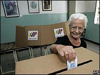 Una electora deposita su voto en una urna de Caracas