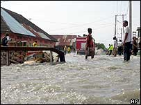Residents stand on a flooded street after tidal waves hit in Lhokseumawe, Aceh province  26/12/04