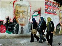 Mujeres pasan frente a un graffiti con el rostro de Abbas