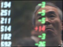 A businessman looks at a Nikkei screen in a shop window