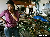 A Thai woman walks by the devastation at a hotel along Patong Beach in Phuket, Thailand