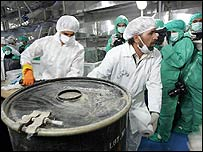 Two technicians carry a box containing yellowcake at the Iranian nuclear facility at Isfahan