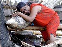 A woman, whose father and son are missing, sobs near Galle in Sri Lanka