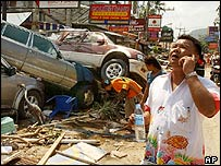 Man talks on his phone next to cars smashed by the water in Patong Beach, Thailand