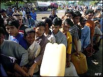 Survivors queue for water
