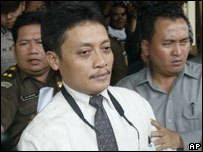 Pollycarpus Priyanto, is escorted by police officers after his trial in Jakarta, Tuesday, 9 Aug 2005
