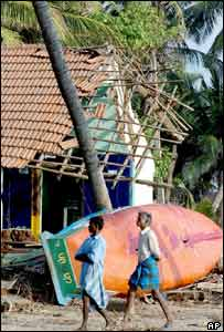Indian fisherman walk past a destroyed house and boat