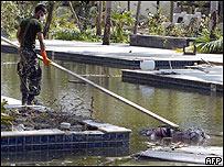 Un efectivo militar tailandés intenta retirar el cuerpo de un turista occidental en una piscina de un centro vacacional (Saeed Khan/AFP/Getty Images)