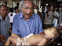 A Sri Lankan man carries body of his son from hospital at the town of Galle, south of Colombo.