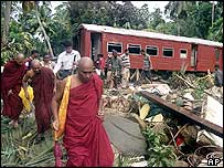 Buddhist monks trudge away from the wrecked train