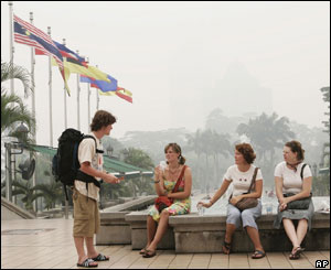 Tourists sit at the entrance to Kuala Lumpur Tower, 10 August