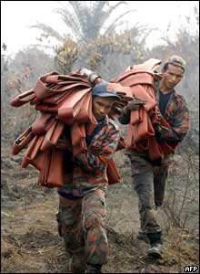 Malaysian firemen walk across scorched earth after battling vast peat fires in a palm oil plantation south of Kuala Lumpur, 6 August 2005.