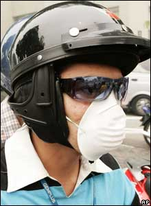 Motorists cover their mouths to protect themselves from smoky haze in downtown Kuala Lumpur, 10 August 2005.