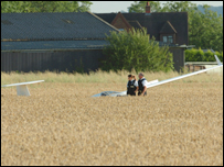 Police officers and glider in field