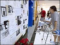 People study posters in a hospital of people missing in Phuket, southern Thailand