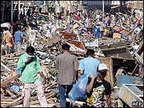 Survivors searching through destroyed buildings