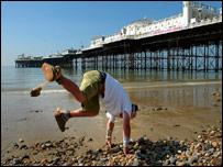 Mark McGowan attempting a cartwheel in Brighton