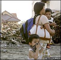 Madre con dos hijos en medio de los escombros.