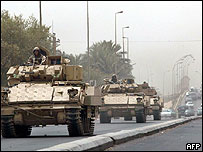 US armoured vehicles drive along the airport road in west Baghdad