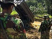 Trucks dump bodies into mass grave