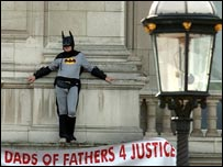 A man dressed as Batman stands on a balcony at Buckingham Palace
