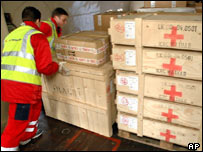 Aid workers load supplies on to cargo plane, AP