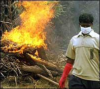 A Tamil Tiger walks away from a funeral pyre in Mullaitivu
