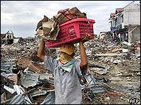 An Indonesian man carries some belongings from his damaged shop in Banda Aceh