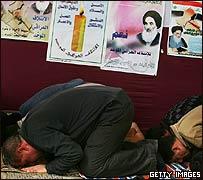 Fieles rezando frente a una pared llena de afiches políticos.
