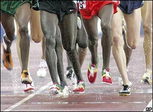 Piernas de los corredores sobre una pista mojada.