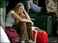 A girl waits with her luggage