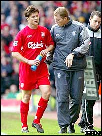 Liverpool midfielder Xabi Alonso is assisted off the pitch after breaking his ankle