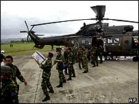 Indonesian soldiers load relief supplies onto a Singaporean helicopter at Banda Aceh airport.