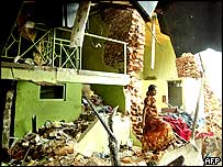 A woman walks among the rubble in her destroyed shop in the south-western Sri Lankan coastal town of Galle.