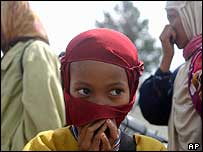 A child covers her nose from the stench of dead bodies in a refugee camp in Banda Aceh, Indonesia