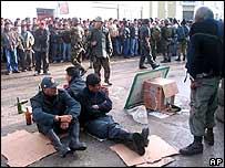 Tres de los policías secuestrados sentados en la calle mientras miembros del Movimiento Etnocacerista, con vestimenta militar, los rodean
