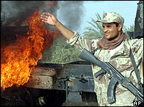 An Iraqi National Guard next to a burning US Army supply truck on the outskirts of Balad, 14 October 2004
