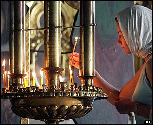 Woman lights candle at church ceremony